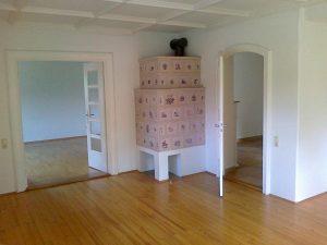 Wohnzimmer vor der Renovierung mit altem Kachelofen
